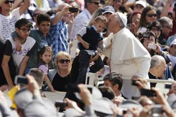 Pope Francis kisses a child as he arrives to lead his Wednesday general audience in Saint Peter's Square at the Vatican June 5, 2013. REUTERS/Max Rossi