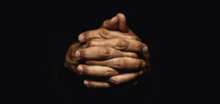 Male hands crossed for prayer in dark