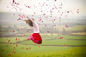 Girl jumping with rose petals in air